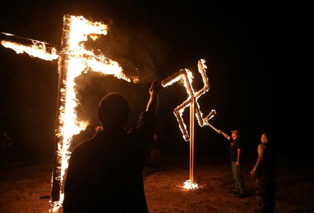 Members of the ShieldWall Network, a white nationalist group, burn a swastika and cross during a party outside Atkins, Arkansas, U.S., March 9, 2019. REUTERS/Jim Urquhart