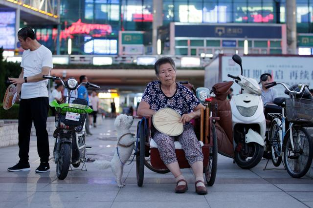 FILE PHOTO: A 68-year-old woman with a stroke sits in a tricycle as she rests at a city square in Weifang, Shandong province, China, July 24, 2019. REUTERS/Jason Lee