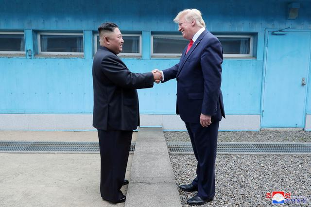 FILE PHOTO: U.S. President Donald Trump shakes hands with North Korean leader Kim Jong Un as they meet at the demilitarized zone separating the two Koreas, in Panmunjom, South Korea, June 30, 2019. KCNA via REUTERS