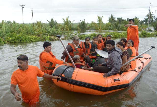 Members of National Disaster Response Force (NDRF) evacuate flood-affected people to a safer place, in Sangliwadi, Sangli district, in the western state of Maharashtra, India, August 10, 2019. REUTERS/Stringer