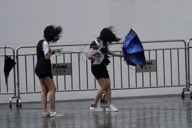 People walk in the rainstorm as typhoon Lekima approaches in Shanghai, China August 10, 2019. REUTERS/Aly Song