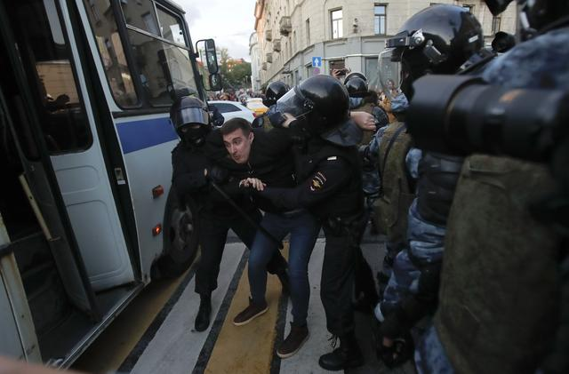 Law enforcement officers detain a man after a rally to demand authorities allow opposition candidates to run in the upcoming local election in Moscow, Russia August 10, 2019. REUTERS/Maxim Shemetov