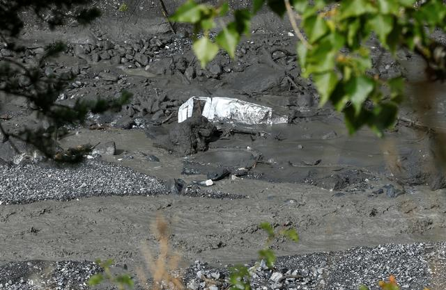 The wreckage of a car is pictured in  the Losentze river after a flash flood in Chamoson, Switzerland, August 12, 2019. REUTERS/Denis Balibouse