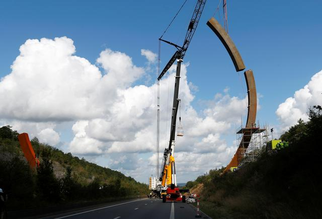 A crane is used to put the last piece of the Arc Majeur, a 60-meter arch designed by French artist Bernar Venet and installed on the E411 highway in Lavaux-Sainte-Anne, Belgium, August 13, 2019.  REUTERS/Francois Lenoir