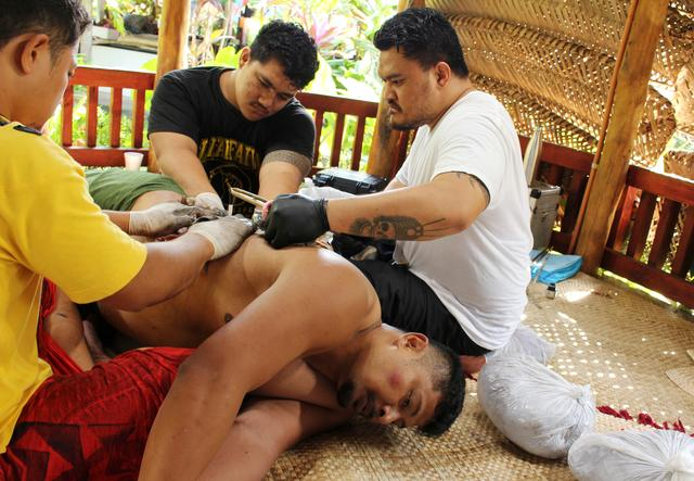 Oliver Fagalilo receives a traditional tattoo delivered by Samoan tattoo artist Li'aifva Imo Leni in Apia, Samoa, July 15, 2019.  REUTERS/Jonathan Barrett