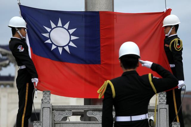 FILE PHOTO: Military honour guards attend a flag-raising ceremony at Chiang Kai-shek Memorial Hall, in Taipei, Taiwan March 16, 2018. REUTERS/Tyrone Siu/File Photo