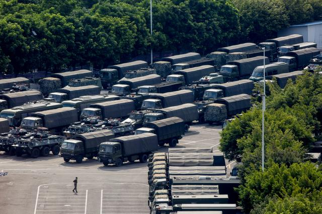 Servicemen walk past military vehicles in the parking area of the Shenzhen Bay Sports Center in Shenzhen across the bay from Hong Kong, China August 16, 2019.  REUTERS/Thomas Peter