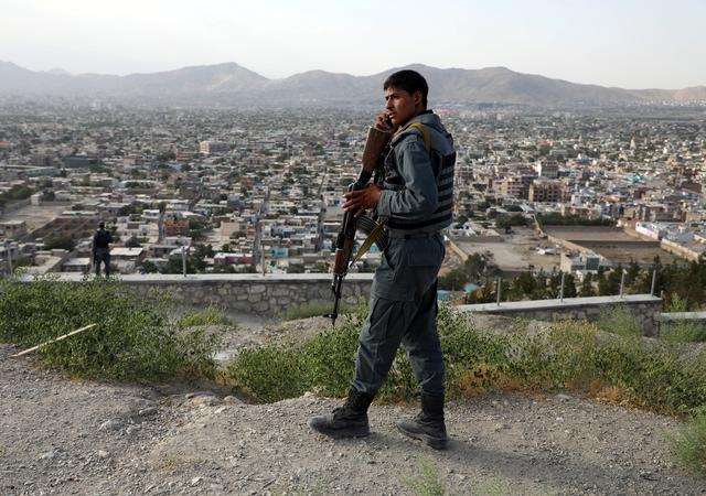 FILE PHOTO: An Afghan policeman keeps watch at a hilltop in Kabul, Afghanistan July 23, 2019.REUTERS/Omar Sobhani/File Photo
