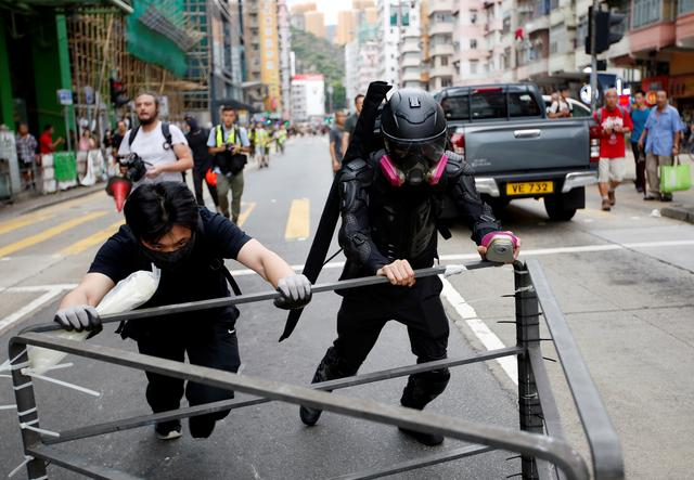 A protester nicknamed Ah Lung and another protester push a barricade to the frontline during a protest in Sham Shui Po neighbourhood of Hong Kong, China August 11, 2019.    REUTERS/James Pomfret