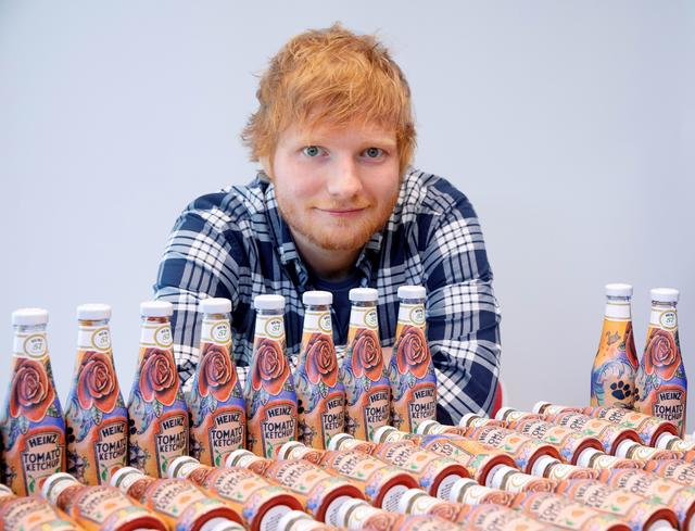 Ed Sheeran poses with bottles of Heinz Tomato Ketchup based on his tattoos in London, Britain May 20, 2019, in this handout photo. Heinz/Handout via REUTERS