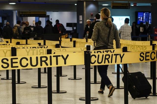 FILE PHOTO: Passengers make their way in a security checkpoint at the International JFK airport in New York October 11, 2014. REUTERS/Eduardo Munoz