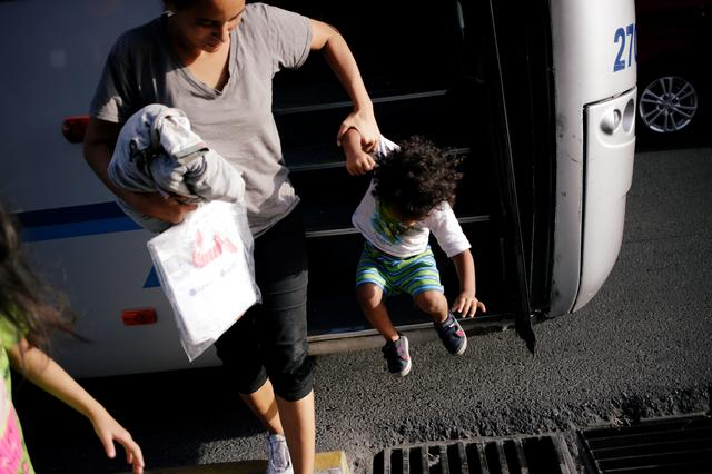 FILE PHOTO: Central American migrants, returned from the U.S. to Nuevo Laredo in Mexico under the Migrant Protection Protocol (MPP) to wait for their court hearing for asylum seekers, are seen arriving to Monterrey, Mexico July 31, 2019.  REUTERS/Daniel Becerri
