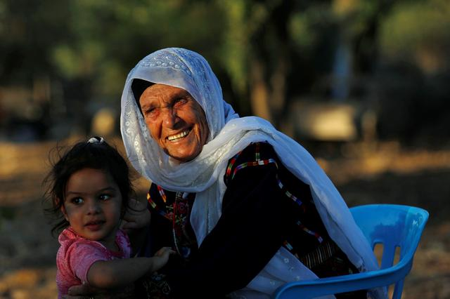 Muftia, the grandmother of U.S. congresswoman Rashida Tlaib, is seen with her granddaughter outside her house in the village of Beit Ur Al-Fauqa in the Israeli-occupied West Bank August 16, 2019. Picture taken August 16, 2019.  REUTERS/Mohamad Torokman