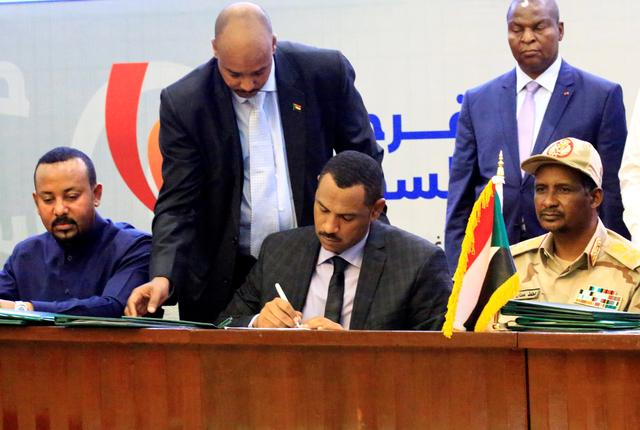 Deputy Chairman of the Sudanese Transitional Military Council, Mohamed Hamdan Dagalo, and Sudan's opposition alliance coalition's leader Ahmad al-Rabiah, sign a power sharing deal, as Ethiopia's Prime Minister Abiy Ahmed witnesses, in Khartoum, Sudan, August 17, 2019. REUTERS/Nureldin Mohamed Abdallah