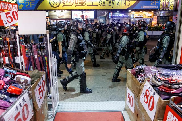 Riot police walk past a shop as they chase anti-government protesters down Nathan Road in Mong Kok in Hong Kong, China August 17, 2019.  REUTERS/Thomas Peter