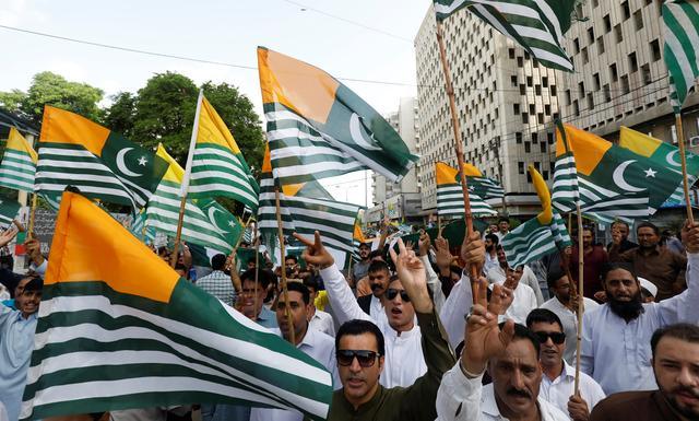 People carry Azad Kashmir's flags and chant slogans over India's decision to revoke the special status of Jammu and Kashmir, during a protest in Karachi, Pakistan August 18, 2019. REUTERS/Akhtar Soomro