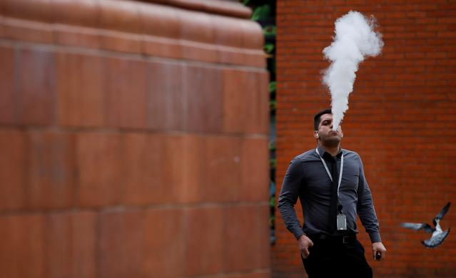 FILE PHOTO: A man vapes outside an office block in Manchester, Britain, February 6, 2019. REUTERS/Phil Noble/File Photo