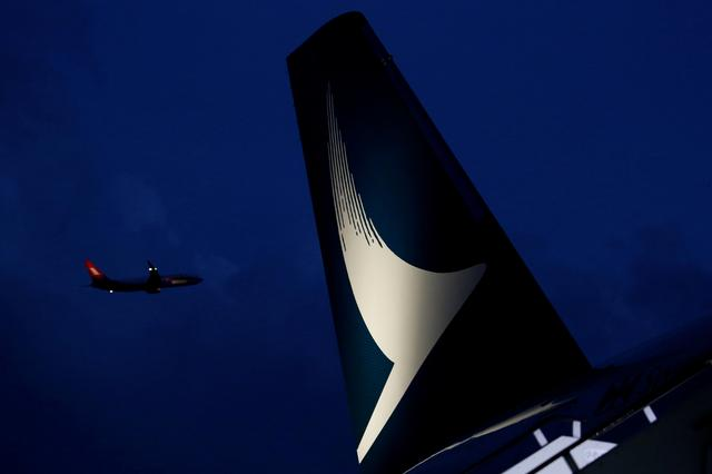 FILE PHOTO: A plane flies behind a new Cathay Pacific Airways Airbus A350 after being received by the airline at Hong Kong Airport, China May 30, 2016.   REUTERS/Bobby Yip/File Photo