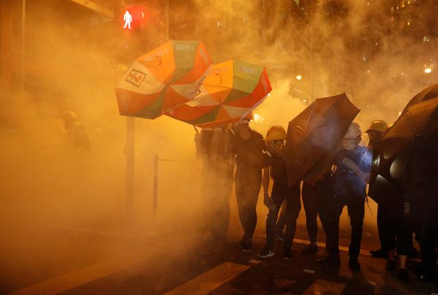 Pro-democracy protesters shield themselves with umbrellas in tear gas as they clash with police in Hong Kong, China July 28, 2019. REUTERS/Edgar Su