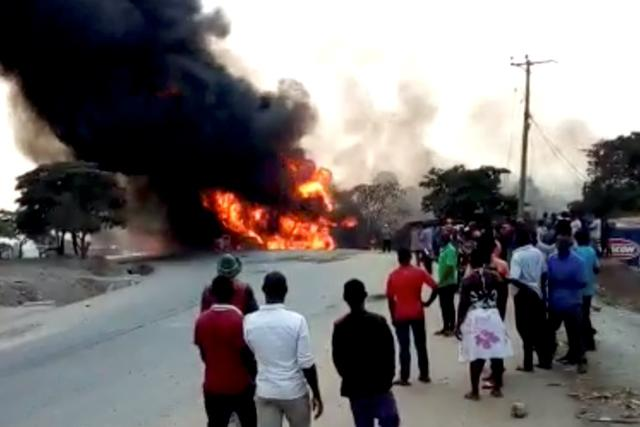 People look towards a fire following a fuel truck collision in Rubirizi, Uganda August 18, 2019 in this still image taken from social media video. Nayebare Ediger via REUTERS