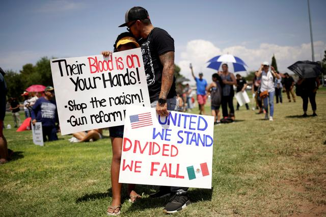 FILE PHOTO: People embrace while holding placards during a rally against the visit of U.S. President Donald Trump after last weekend's shooting at a Walmart store, in El Paso, Texas, U.S., August 7, 2019. REUTERS/Jose Luis Gonzalez