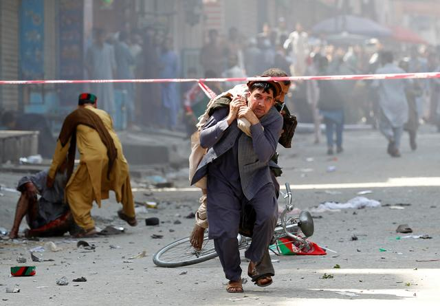 A man caries a wounded person to the hospital after a blast in Jalalabad, Afghanistan August 19, 2019. REUTERS/Parwiz