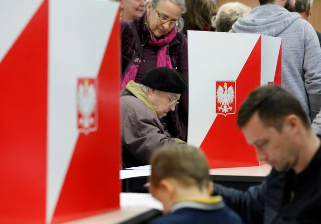 FILE PHOTO: People attend the Polish regional elections, at a polling station in Warsaw, Poland, October 21, 2018. REUTERS/Kacper Pempel