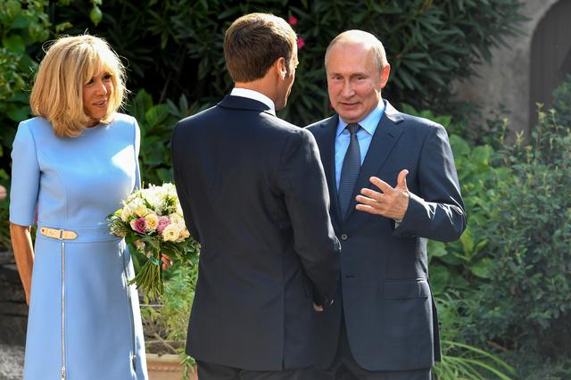 French President Emmanuel Macron (C) and his wife Brigitte Macron (L) welcome Russia's President Vladimir Putin, at the French President's summer retreat of the Bregancon fortress on the Mediterranean coast, near the village of Bormes-les-Mimosas, southern France, on August 19, 2019. Gerard Julien/Pool via REUTERS