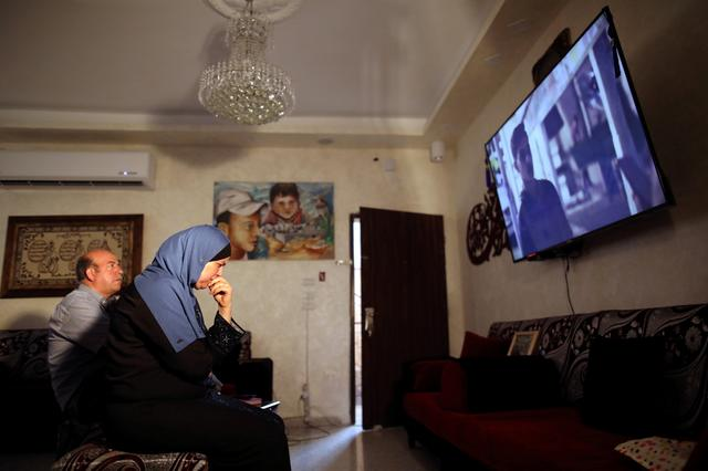 "Hussein and Suha Abu Khdeir, whose son's murder is the subject of the HBO series ""Our Boys"", watch the show's first two episodes in their East Jerusalem home August 18, 2019. REUTERS/Ammar Awad"