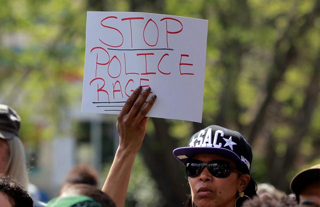FILE PHOTO: A demonstrator holds a sign at a rally to protest the police shooting of Stephon Clark, in Sacramento, California, U.S., March 31, 2018.  REUTERS/Bob Strong/File Photo