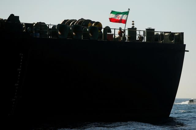A crew member raises the Iranian flag on Iranian oil tanker Adrian Darya 1, previously named Grace 1, as it sits anchored after the Supreme Court of the British territory lifted its detention order, in the Strait of Gibraltar, Spain, August 18, 2019. REUTERS/Jon Nazca