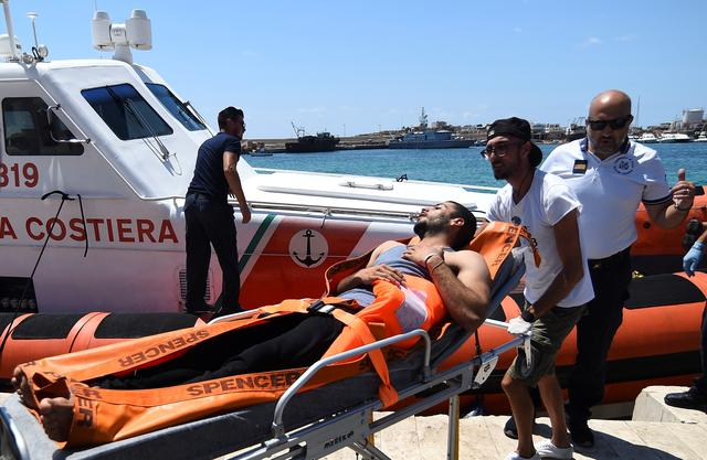 A migrant who jumped off the Spanish rescue ship Open Arms is carried on a stretcher, in Lampedusa, Italy August 20, 2019. REUTERS/Guglielmo Mangiapane