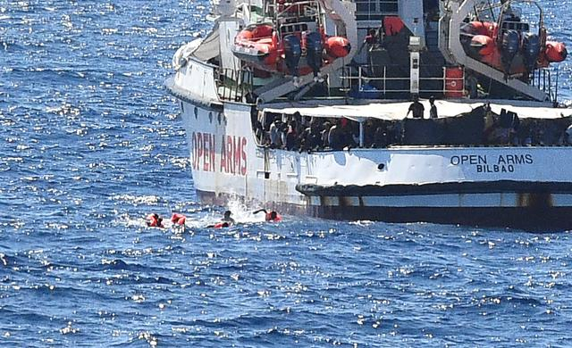 Migrants swim after jumping off the Spanish rescue ship Open Arms, close to the Italian shore in Lampedusa, Italy August 20, 2019. REUTERS/Guglielmo Mangiapane