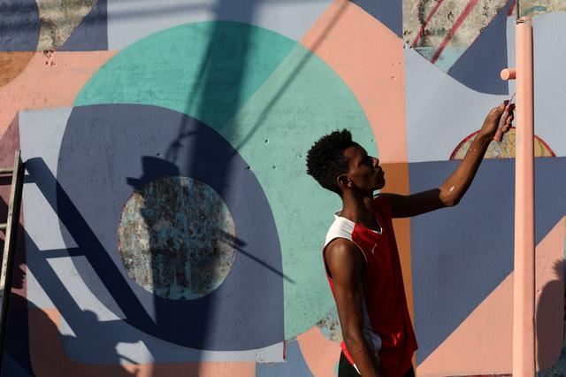FILE PHOTO: A community member helps to artist Fabian Solymar to paint a mural in a wall at the slum of Petare, in Caracas, Venezuela August 7, 2019. REUTERS/Manaure Quintero