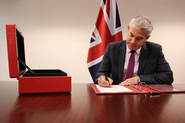 Brexit Secretary Stephen Barclay signs the commencement agreement to leave the EU, in undisclosed location August 16, 2019,  in this picture obtained from social media. STEVE BARCLAY/via REUTERS