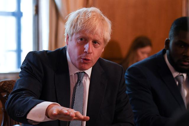 FILE PHOTO: Britain's Prime Minister Boris Johnson speaks next to Youth Justice Board Adviser Roy Sefa-Attakora during a roundtable on the criminal justice system at 10 Downing Street in London, Britain August 12, 2019. Daniel Leal-Olivas/Pool via REUTERS/File Photo