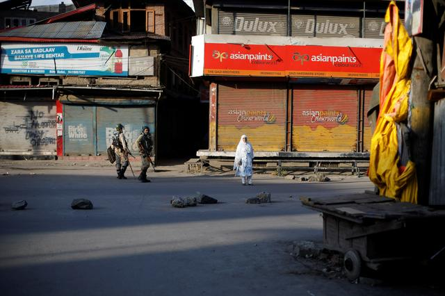 Indian security force personnel patrol past a Kashmiri woman in a deserted street during restrictions after scrapping of the special constitutional status for Kashmir by the Indian government, in Srinagar, August 20, 2019. REUTERS/Adnan Abidi