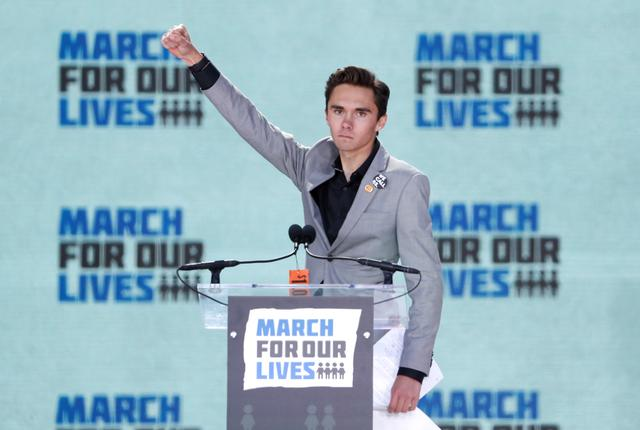 """FILE PHOTO: David Hogg, a student at the Marjory Stoneman Douglas High School, site of a February mass shooting which left 17 people dead in Parkland, Florida, thrusts his fist in the air as he speaks during the """"March for Our Lives"""" event demanding gun control after recent school shootings at a rally in Washington, U.S., March 24, 2018. REUTERS/Aaron P. Bernstein/File Photo"""