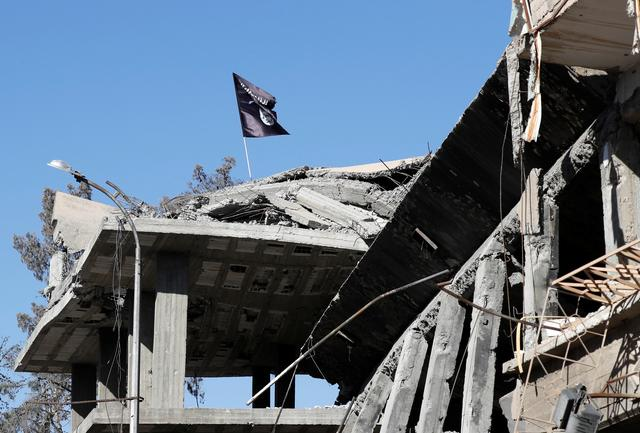 FILE PHOTO: A flag of Islamic State militants is pictured above a destroyed house near the Clock Square in Raqqa, Syria October 18, 2017. Picture taken October 18, 2017.     REUTERS/Erik De Castro