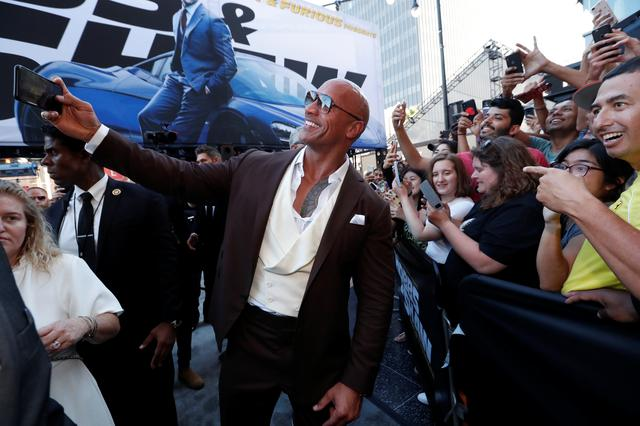 "Cast member and producer Dwayne Johnson takes photos with fans at the premiere for ""Fast & Furious Presents: Hobbs & Shaw"" in Los Angeles, California, U.S., July 13, 2019. REUTERS/Mario Anzuoni"