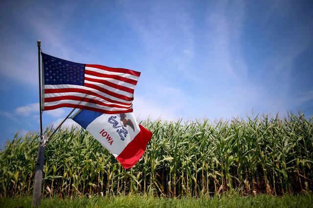FILE PHOTO: U.S. and Iowa state flags are seen next to a corn field in Grand Mound, Iowa, United States, in this August 16, 2015 file photo.    REUTERS/Jim Young/Files/File Photo