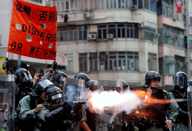 FILE PHOTO: Police officers fire tear gas as anti-extradition bill protesters demonstrate in Sham Shui Po neighbourhood in Hong Kong, China, August 11, 2019. REUTERS/Tyrone Siu/File Photo