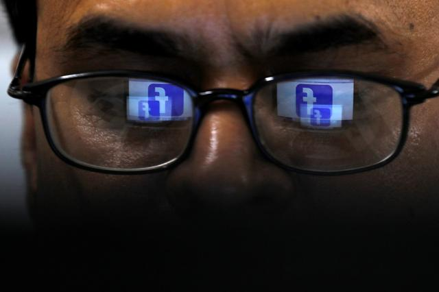 Facebook logo is reflected in glasses in this picture illustration taken April 1, 2019. REUTERS/Akhtar Soomro/Illustration