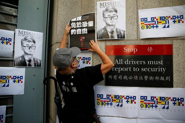 FILE PHOTO: A demonstrator puts a poster on the wall of British Consulate-general office, next to the image of  Simon Cheng, a staff member at the consulate who went missing on August 9 after visiting the neighbouring mainland city of Shenzhen, during a protest outside in Hong Kong, China, August 21, 2019. REUTERS/Willy Kurniawan