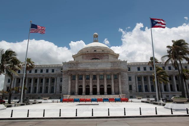 FILE PHOTO: The flags of the U.S. and Puerto Rico fly outside the Capitol building in San Juan, Puerto Rico, May 4, 2017. REUTERS/ Alvin Baez/File Photo
