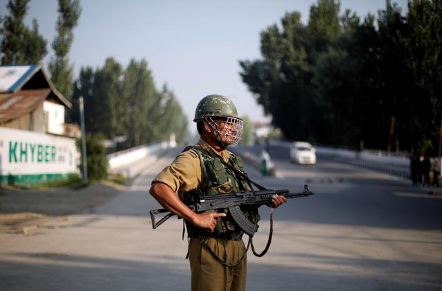 An Indian security personnel stands guard on a deserted road during restrictions after scrapping of the special constitutional status for Kashmir by the Indian government, in Srinagar, August 23, 2019. REUTERS/Adnan Abidi