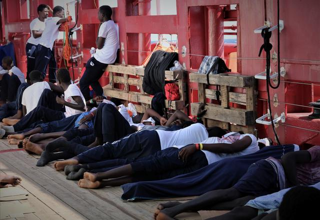 FILE PHOTO: Rescued migrants rest aboard the Ocean Viking, run by French charities Medecins Sans Frontieres and SOS Mediterranee, as it waits in international waters between Malta and the southern Italian island of Linosa for access to a port in this handout picture taken between August 9 and 12, 2019. Ocean Viking/Handout via REUTERS