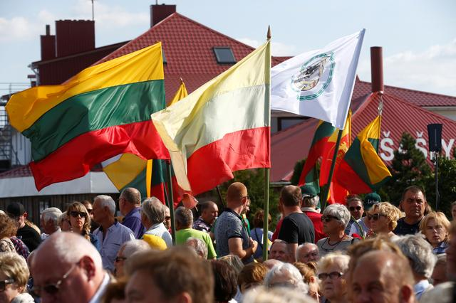 People hold Lithuanian flags during an event to commemorate the anniversary of the Baltic Way on the border with Latvia near Salociai, Lithuania August 23, 2019. REUTERS/Ints Kalnins