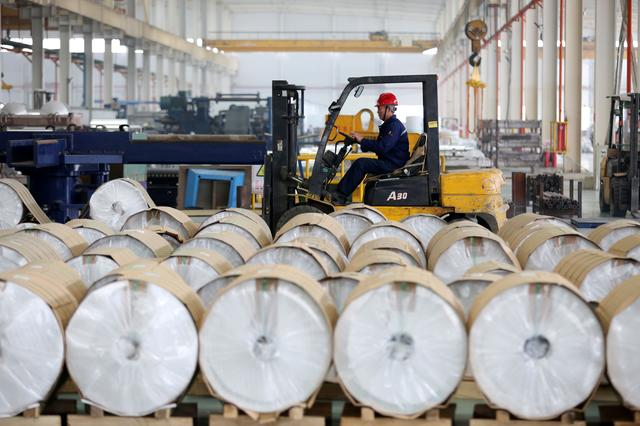 FILE PHOTO: A worker drives a forklift past aluminum rolls at a factory in Huaibei, Anhui province, China March 2, 2019. Picture taken March 2, 2019. REUTERS/Stringer