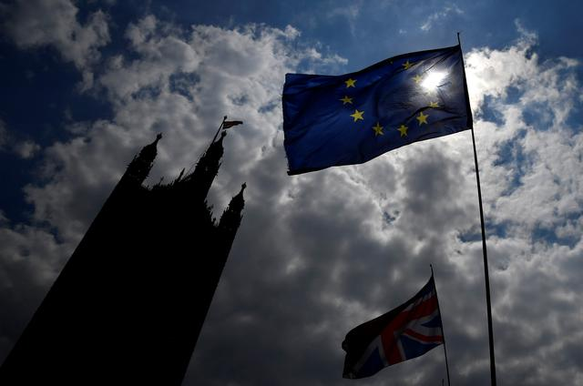 An EU flag and a British Union Jack flag are seen flying near the Houses of Parliament in London, Britain, May 16, 2019. REUTERS/Toby Melville